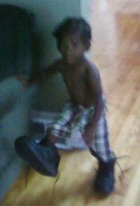 Elijah tries on my giant sneakers